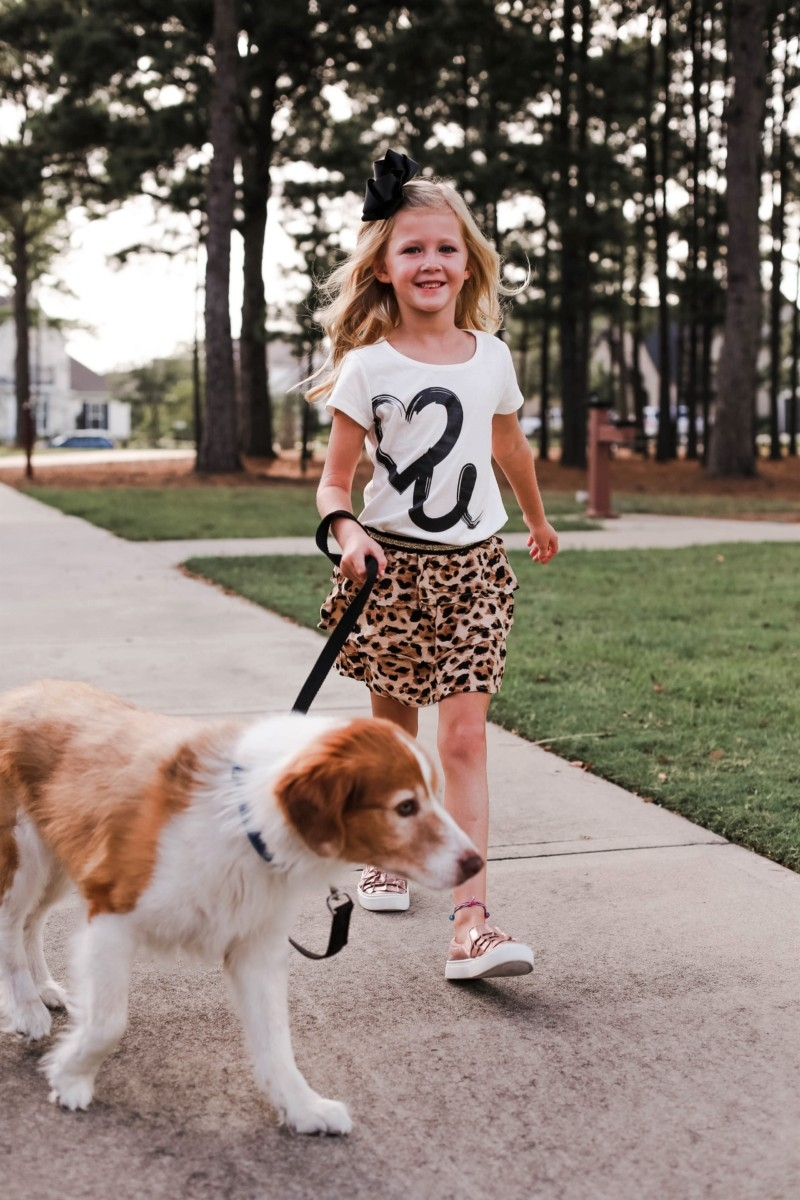 Walmart Fall Clothing: Girls Animal Print Favorites by popular Houston fashion blog, Haute and Humid: image of a girl walking her dog and wearing a Walmart 365 Kids From Garanimals Girls' Skort and Walmart metallic rose gold ruffle sneakers.