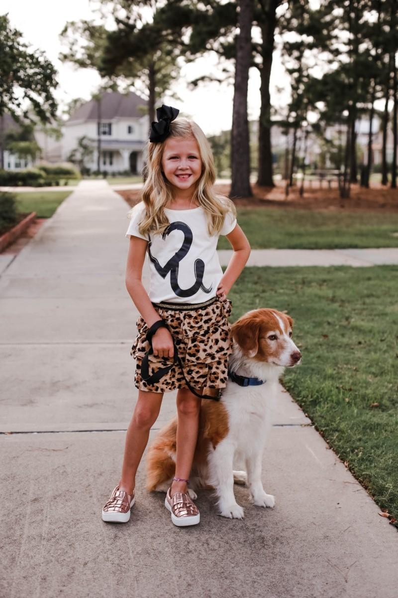 Girls Animal Print Clothes | Walmart Fall Clothing: Girls Animal Print Favorites by popular Houston fashion blog, Haute and Humid: image of a girl walking her dog and wearing a Walmart 365 Kids From Garanimals Girls' Skort and Walmart metallic rose gold ruffle sneakers.