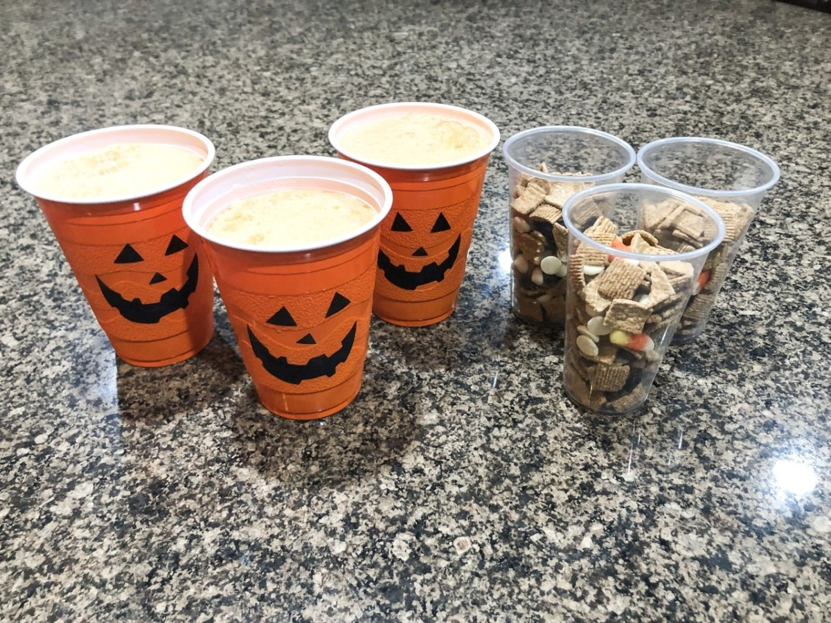 Halloween Family Fun Night | Easy Halloween Activities for Families by popular Houston lifestyle blog, Haute and Humid: image of plastic pumpkins cups with a beverage in it next two clear plastic cups with Halloween trail mix in them.